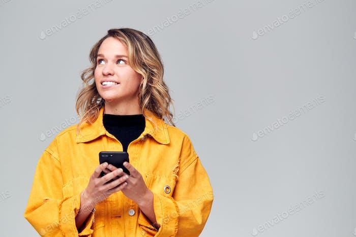 Studio Schuss von Kausally gekleidet junge Frau mit Handy Blick aus Kamera