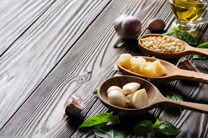 Closeup view at wooden spoons with food ingredients for genovese pesto sauce on kitchen table