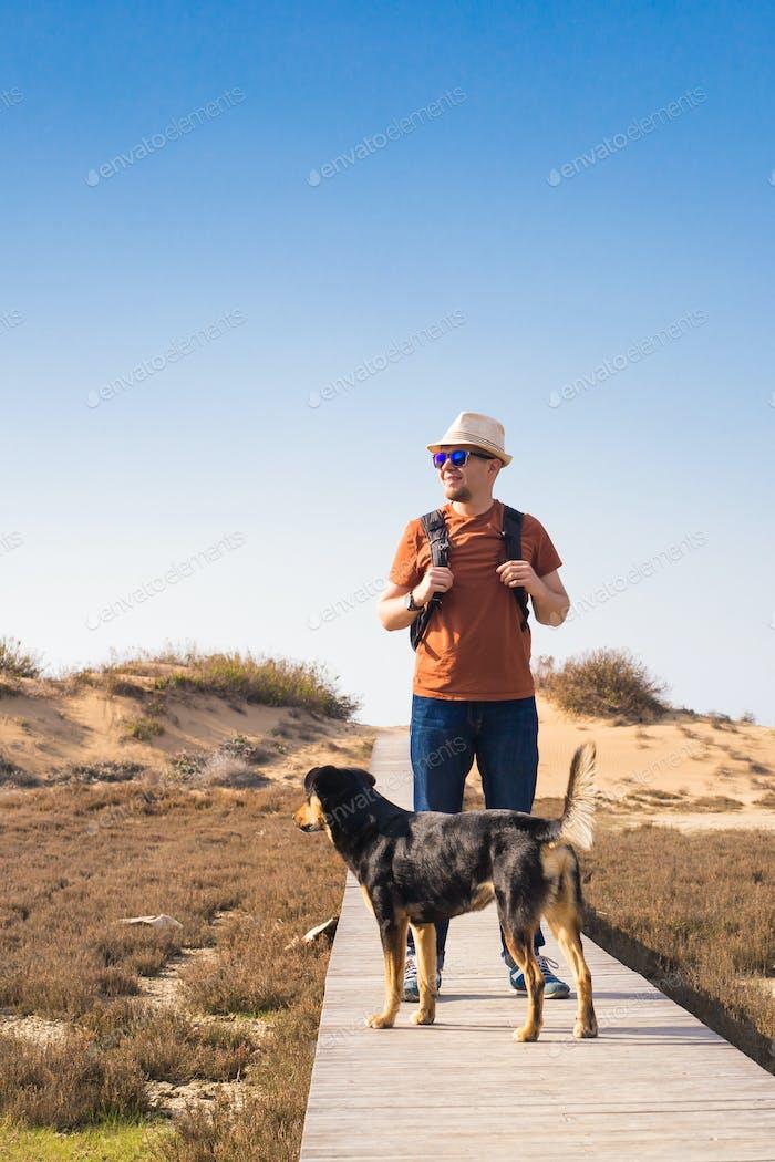 Hombre caminando con su perro en un Carretera que conduce a través de hermoso Horizontal
