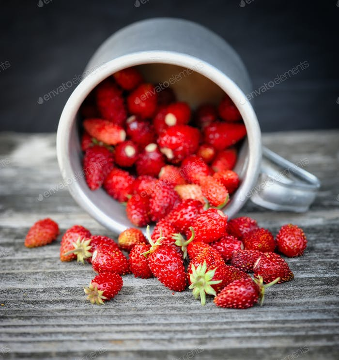 Fresh wild strawberries on an old wooden table