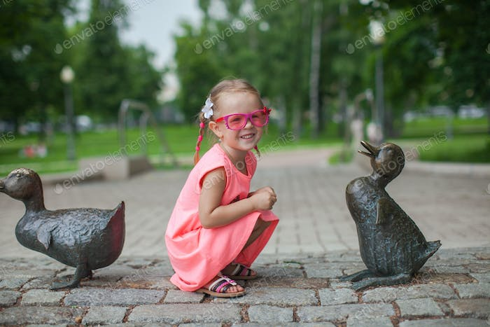 Cute girl sits next a duck figure of iron and having fun