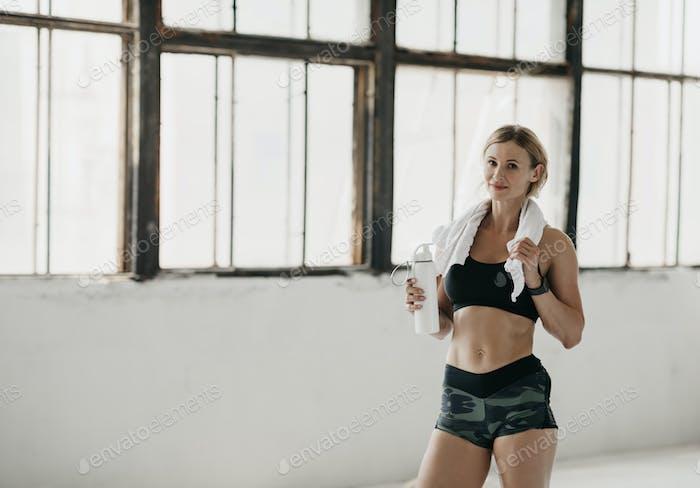 Effektives Training und schöner Körper. Muskulöse Frau in Sportbekleidung mit Fitness-Tracker ruhen