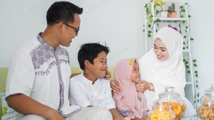 Asian Muslim families celebrate Eid together while enjoying a meal