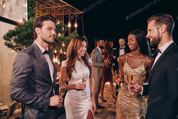Group of people in formalwear communicating and smiling while spending time on luxury party