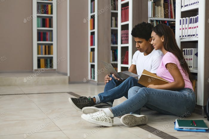 Young couple of black students studying on floor in library