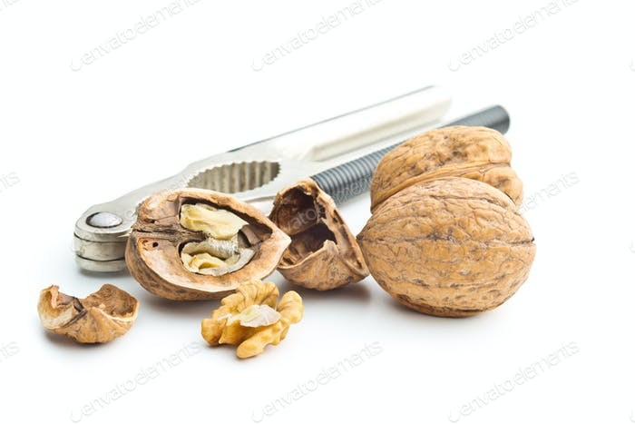 Cracked dried walnuts and nutcracker.