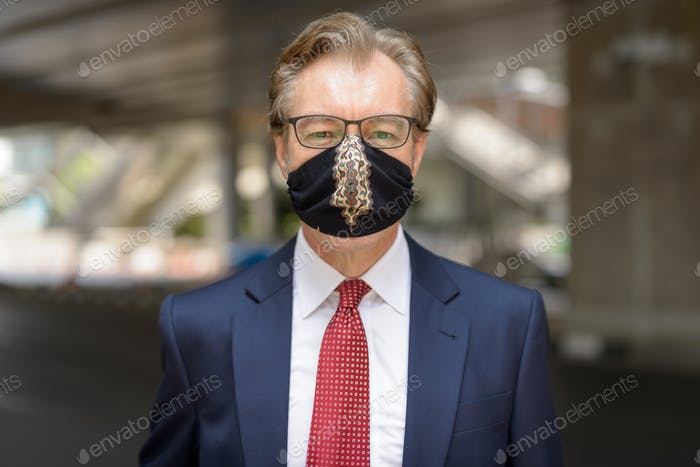 Face of mature businessman wearing mask for protection from corona virus outbreak in the city