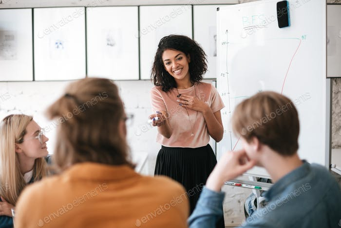 Young smiling business woman giving presentation to her coworkers