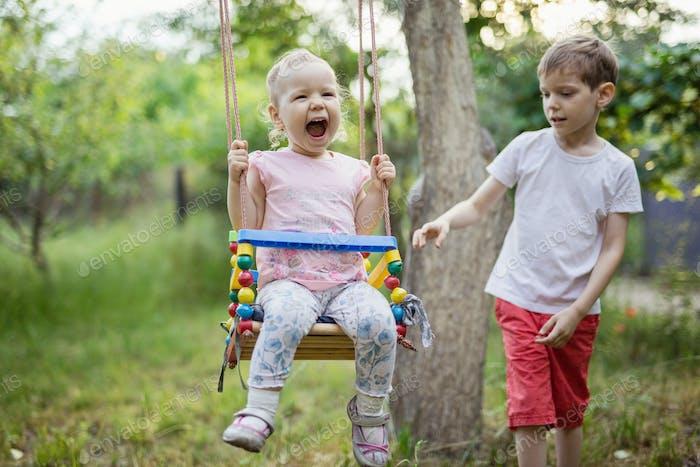 Young boy pushing toddler sister on swing