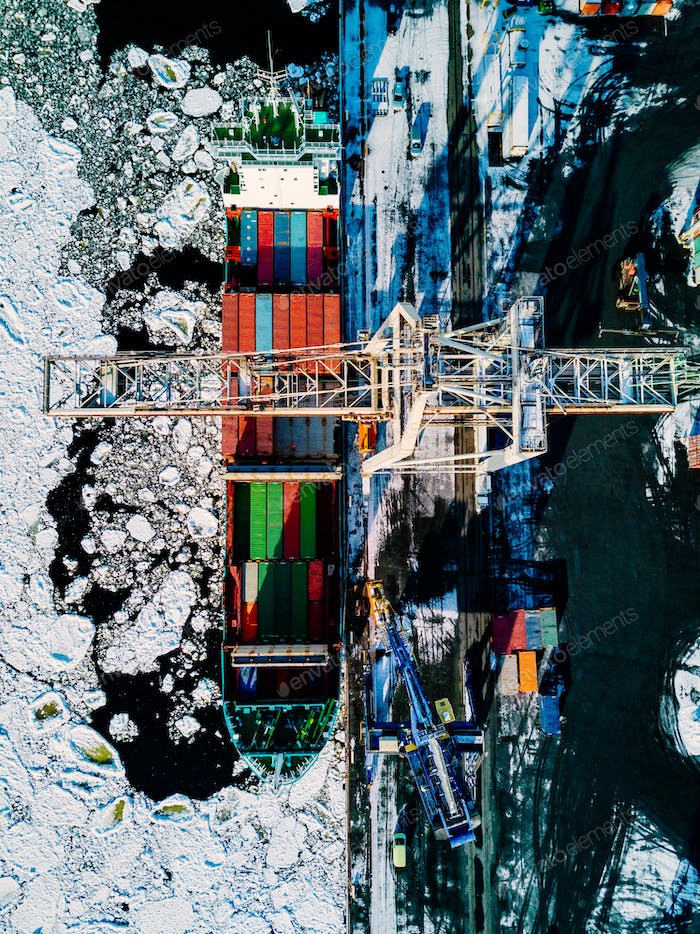 Industrial port with containers in winter, vessel loading