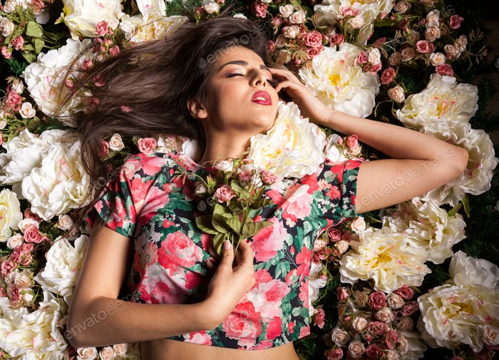 Sexy woman lying on flowers