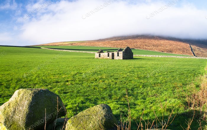 Old and Unfinished Stone House in a Grassy Field in Northern Ireland