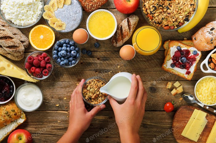 Girl cooking breakfast - granola with yogurt, fruits, berries, milk, yogurt, juice, cheese. Top view