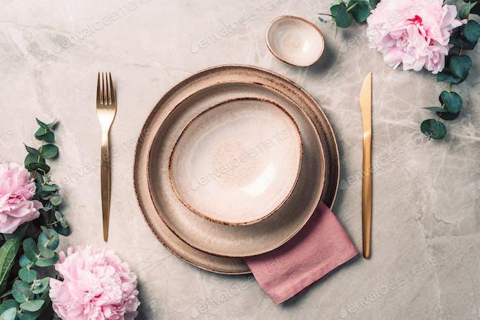 Tableware, flowers for serving a festive table, dinner. Stoneware plates, golden cutlery, eucalyptus