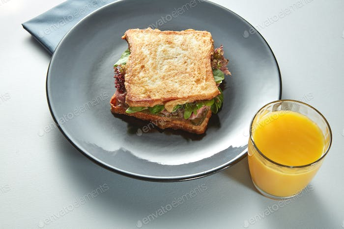 plate with grilled sandwich and orange juice