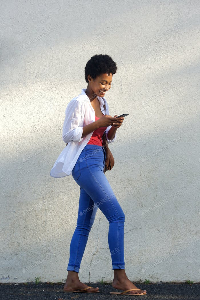 Happy young african woman walking on street using mobile phone