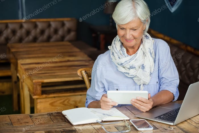Woman using digital tablet while sitting at table in cafe