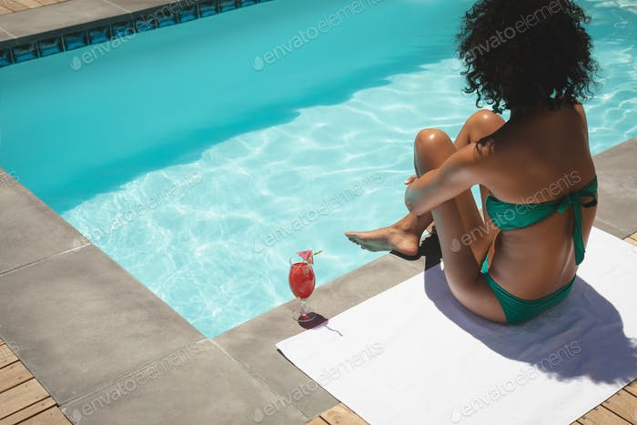 Beautiful young African American woman sitting at poolside in her backyard on a sunny day