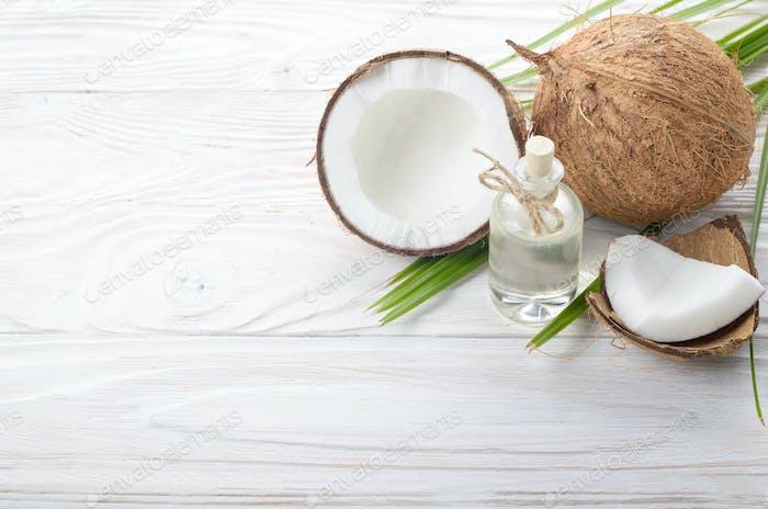 Kokosöl in Glasgefäß und Muschelstücke auf weißem Holztisch