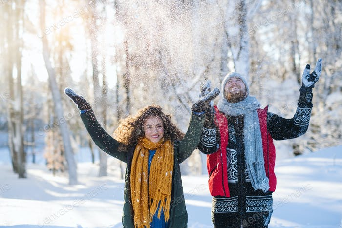 Portrait of couple standing outdoors in snow in winter forest, throwing snow