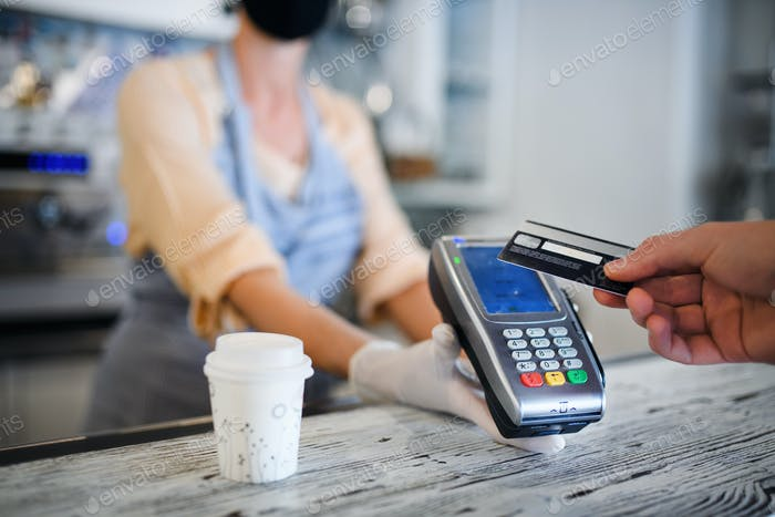 Contactless payment with debit card, coffee shop open after lockdown