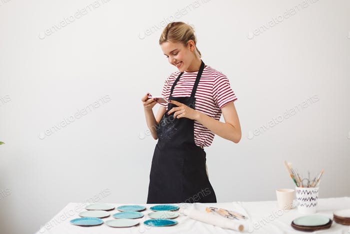 Girl in black apron and striped T-shirt happily taking photos of handmade plates on her cellphone