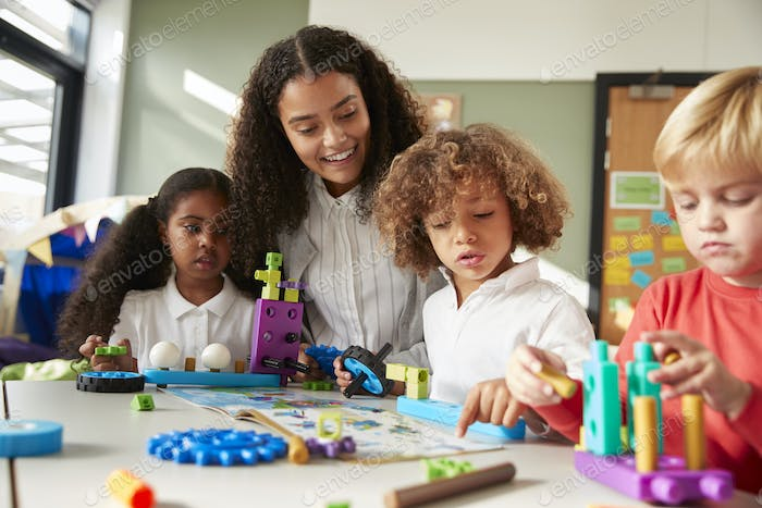 Female teacher sitting at table in play room with three kindergartne children constructing