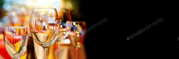 Romantic xmas restaurant interior with beautiful crockery tableware. Crystal wine glasses holidays