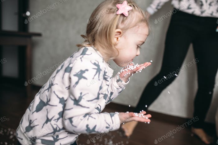 Little girl is playing with foam balls