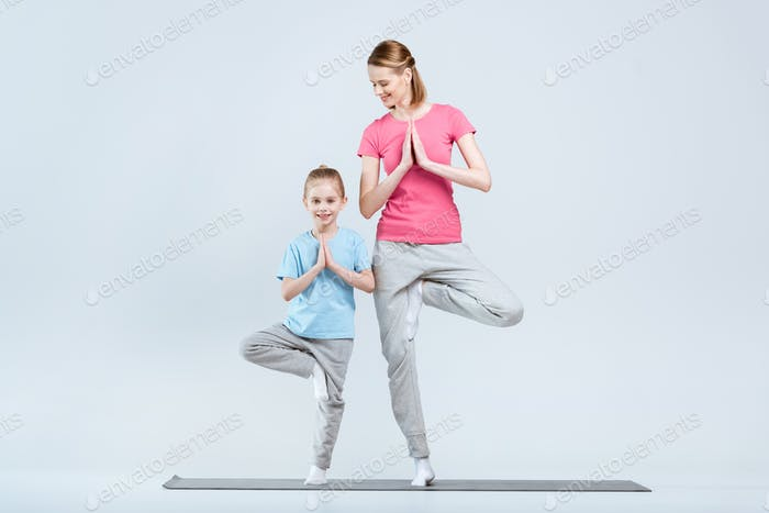 Smiling sporty mother and daughter practicing yoga together, Vrikshasana yoga pose or tree pose
