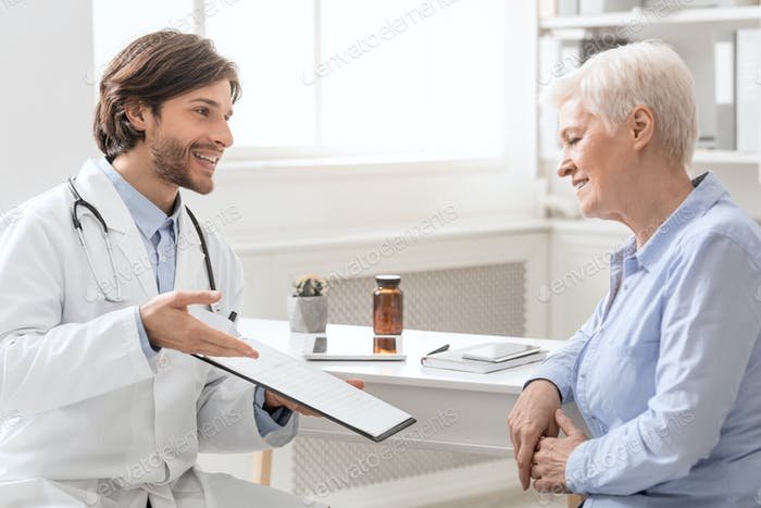 Cheerful doctor explaining treatment plan to senior female patient