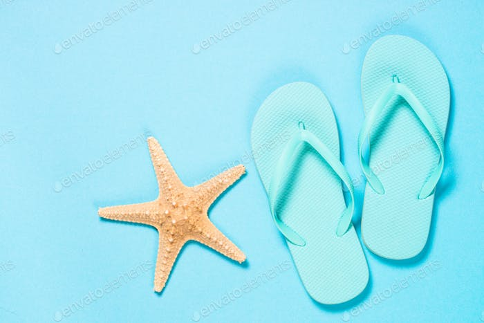 Blue flip flops, sunglasses and starfish on blue background