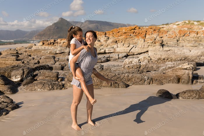 Side view of beautiful young mother giving piggyback to her daughter on beach