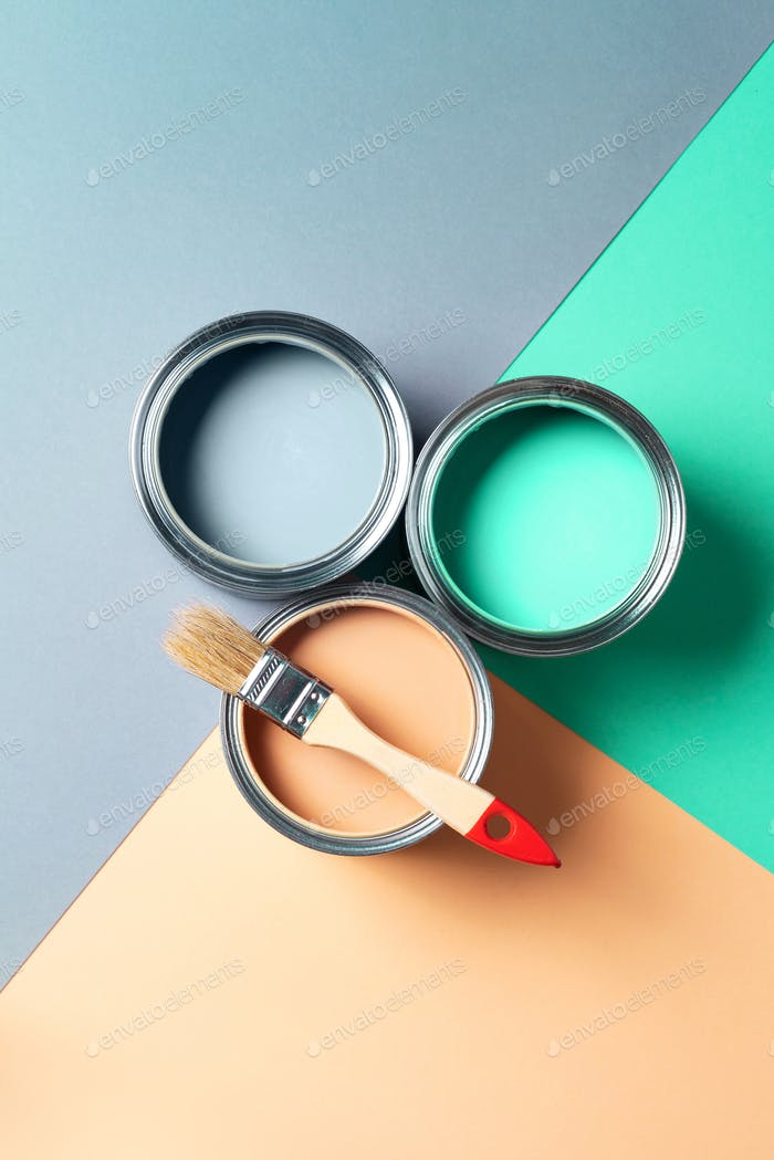 Metal paint cans and paint brushes on multicolor background. Top view. Copy space. Trendy green
