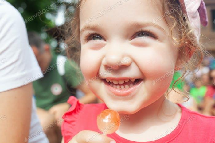 Little girl holding in hand a lollipop