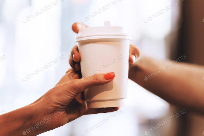 Barista passes coffee to a visitor in a popular coffee shop, hands and a glass of coffee are shot