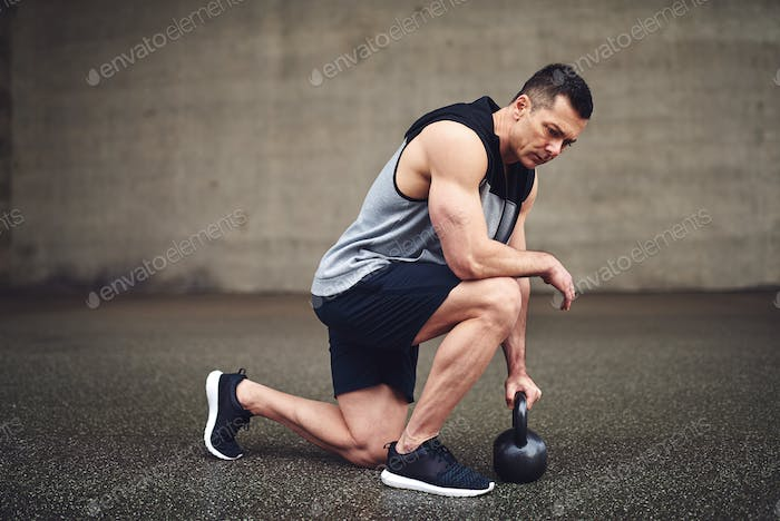 Man in squat with heavy metal kettlebell