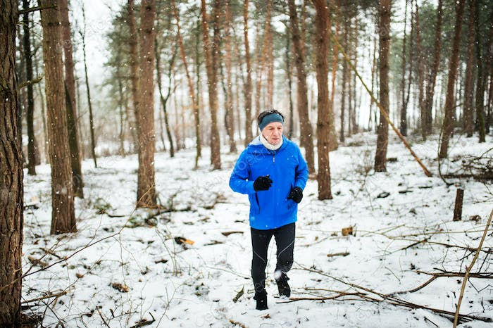 Senior man jogging in woodland in winter nature.