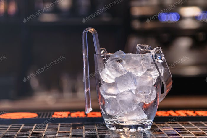 Ice for whiskey in glass bucket on bar counter.