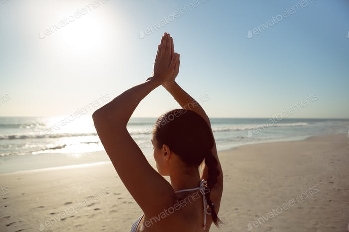 Rear view of woman performing yoga on the beach