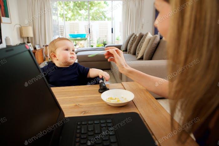 Geschäftsfrau zu Hause arbeiten und füttern Baby