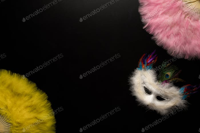 Carnival objects on a black background. Chinese fans, Coiled streamers, masks, confetti