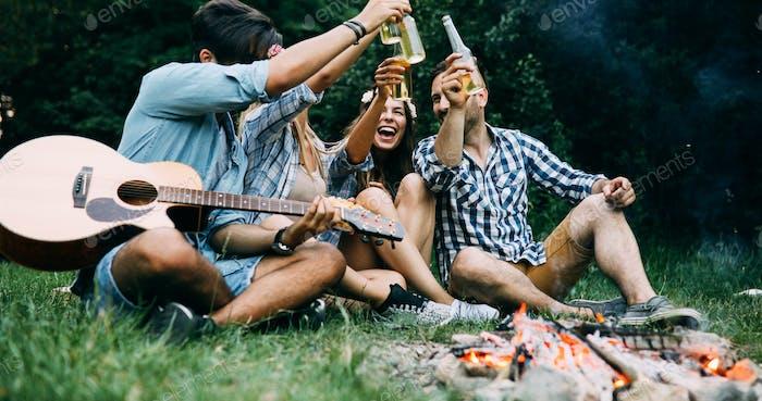Gruppe von Freunden campen und sitzen um Lagerfeuer