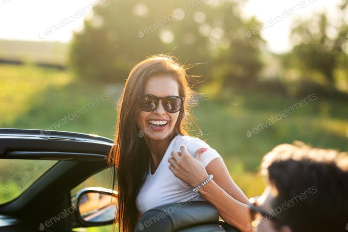 Gorgeous young dark-haired young woman in sunglasses is laughing in a black cabriolet on a sunny day
