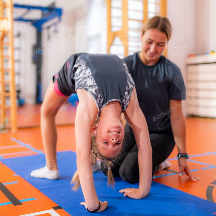 Physical activity for kids, child doing a bridge with a trainer, core strengthening exercise