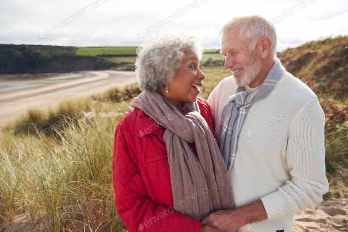Liebevolle aktive Seniorenpaar stehend und umarmt auf spaziergang in sanddünen auf winter strand urlaub
