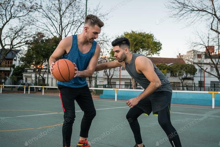 Zwei junge Freunde spielen Basketball.