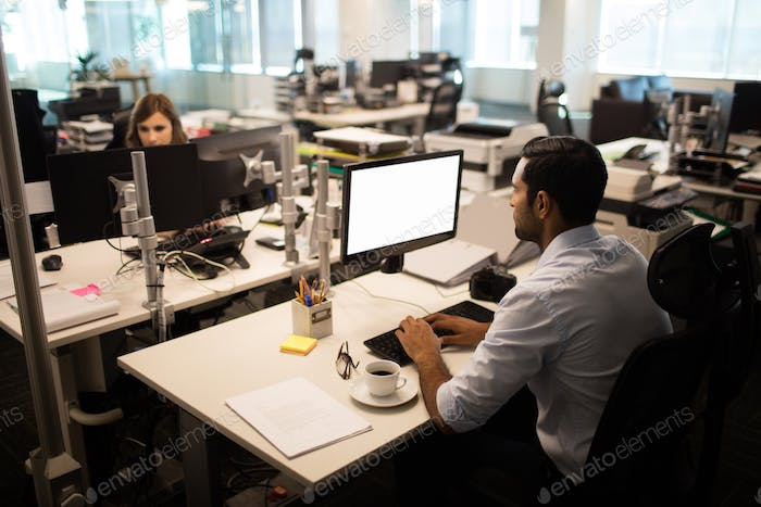 Businessman and businesswoman working in office