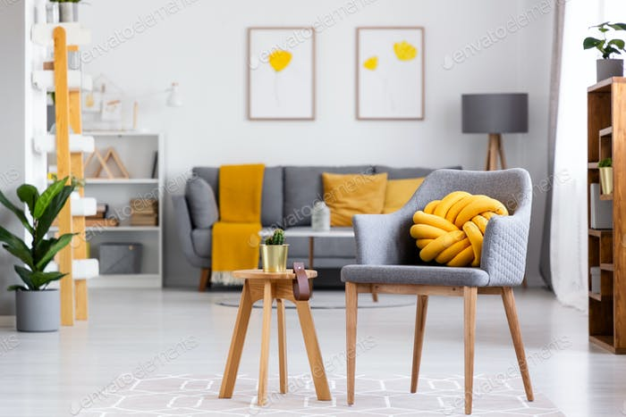 Yellow knot cushion on a gray armchair standing next to a wooden