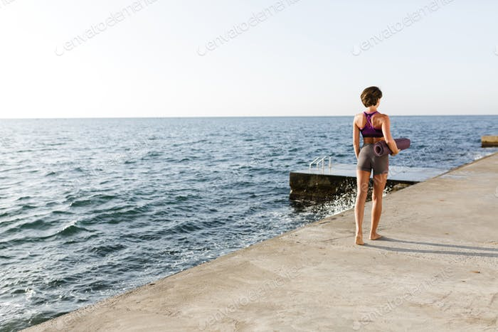 Young woman with dark short hair holding yoga mat in hand while walking by the sea